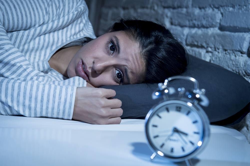 Photo d'une jeune femme ayant un problème de sommeil et étant stressée par son réveil.
